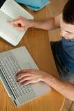 Kursteilnehmer, der Notizbuch für seine Heimarbeit verwendet Lizenzfreie Stockfotografie