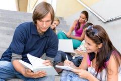 Kursteilnehmer, der seinem Kollegen mit Schulearbeit hilft Lizenzfreie Stockbilder