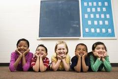 Kursteilnehmer, die auf Fußboden im Klassenzimmer liegen. Stockfoto