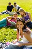 Kursteilnehmer, die das Sitzen auf Gras im Park studieren Stockbilder