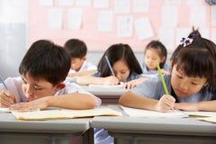 Kursteilnehmer, die an den Schreibtischen in der chinesischen Schule arbeiten Lizenzfreie Stockfotografie