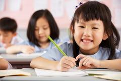 Kursteilnehmer, die an den Schreibtischen in der chinesischen Schule arbeiten Lizenzfreie Stockbilder