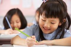 Kursteilnehmer, die an den Schreibtischen in der chinesischen Schule arbeiten stockbild