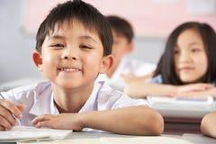 Kursteilnehmer, die an den Schreibtischen in der chinesischen Schule arbeiten Stockbilder
