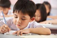 Kursteilnehmer, die an den Schreibtischen in der chinesischen Schule arbeiten Stockfotografie