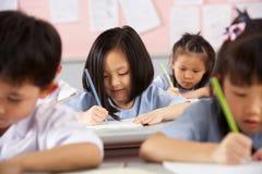 Kursteilnehmer, die an den Schreibtischen in der chinesischen Schule arbeiten Lizenzfreie Stockfotos