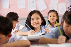 Kursteilnehmer, die an den Schreibtischen in der chinesischen Schule arbeiten Stockfoto