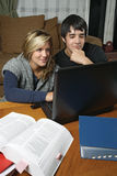 Kursteilnehmer, die Heimarbeit mit Laptop tun Lizenzfreie Stockbilder