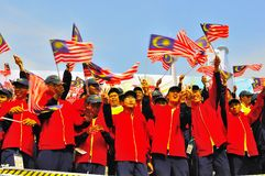 Kursteilnehmer, die Malaysia-Markierungsfahnen während des Nationaltags wellenartig bewegen Stockfotografie