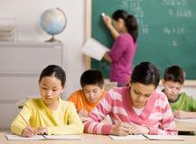 Kursteilnehmer, die in Notizbuch im Schuleklassenzimmer schreiben Lizenzfreie Stockfotos