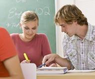 Kursteilnehmer, die zusammen im Klassenzimmer studieren Lizenzfreies Stockfoto