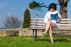 Kursteilnehmer liest das Buch, das auf einer Bank sitzt Stockbilder