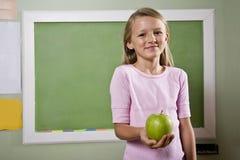 Kursteilnehmer mit Apfel für Lehrer Stockbild
