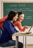 Kursteilnehmer mit dem Laptop, der Heimarbeit mit Freund tut Lizenzfreies Stockfoto