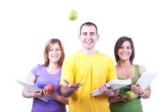 Kursteilnehmer mit Notizbüchern und Äpfeln Lizenzfreie Stockbilder