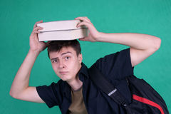 Kursteilnehmer mit schweren Büchern auf seinem Kopf Stockfotografie