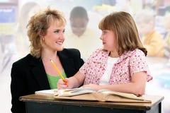Kursteilnehmer und Lehrer am Schreibtisch im Klassenzimmer. Lizenzfreie Stockfotografie