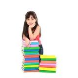 Kursteilnehmermädchen, das auf Stapel der Bücher eaning ist Stockfotografie