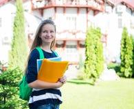 Kursteilnehmermädchen, draußen beim Sommerparklächeln glücklich Junge Frau des Colleges oder des Hochschulstudenten mit Schultasc stockfoto