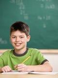 Kursteilnehmerschreiben im Notizbuch im Schuleklassenzimmer stockfoto