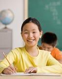 Kursteilnehmerschreiben im Notizbuch im Schuleklassenzimmer Lizenzfreie Stockfotografie
