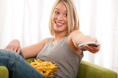 Kursteilnehmerserie - junge blonde Frau, die Fernsieht Stockfoto