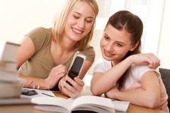 Kursteilnehmerserie - zwei Mädchen, die Handy überwachen Lizenzfreie Stockfotos