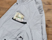 Kurtka i dolary w kieszeni na starym drewnianym stole Zdjęcia Stock