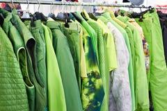 Kurtki, waistcoats i rainwear na wieszaku w sklepie, fotografia stock