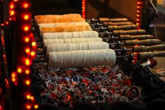 Kurtos kalacs Chimney Cakes baking on roll spinning. Over hot coals at a Christmas market stand Stock Photography