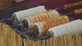 Kurtos Kalacs ? dolce ungherese tradizionale cotto della striscia della pasta di lievito ha avvolto lo zucchero granulato arrivat stock footage