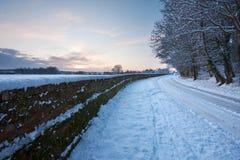 Kurven der schneebedeckten Straße am Sonnenuntergang Stockfoto