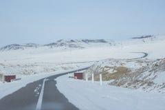 Kurven Sie die Asphaltstraße, die durch Schnee nahe See Khovsgol bei Mongolei umgibt Lizenzfreie Stockfotos