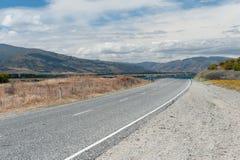 Kurven Sie die Straße, die zum Hügel vorangeht Stockfotos