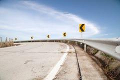 Kurven Sie Straße und unterzeichnen Sie auf unten Hügel, auf blauer Himmel und Wolke backgr Stockfotos