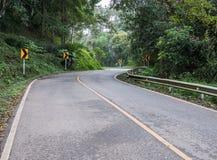 KurvenAsphaltstraße mit dem Richtungszeichen Lizenzfreies Stockbild
