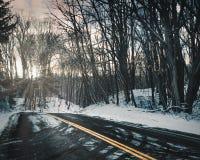 Kurvenreiche Straße bedeckt im Schnee lizenzfreies stockfoto