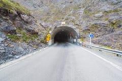 Kurvenstraße, die zum Tunnel vorangeht. Stockbild