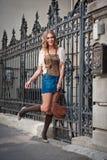 Kurzer Rock und Tasche des Mädchens, die auf Straße geht. Junges europäisches Mädchen in der städtischen Landschaft Stockbild