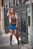 Kurzer Rock und Tasche des Mädchens, die auf Straße geht. Junges europäisches Mädchen in der städtischen Landschaft Lizenzfreies Stockbild