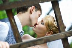 Kus de bruid en de bruidegom bij huwelijksgang Royalty-vrije Stock Foto's