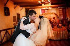 Kus en dans jonge bruid en bruidegom Royalty-vrije Stock Afbeeldingen