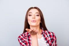 Kus voor u babe! De aantrekkelijke jonge dame verzendt luchtkus naar royalty-vrije stock foto's