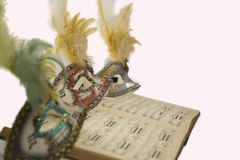 Carnival venetian mask on music page. Royalty Free Stock Image