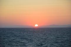 Kusadasi, die Türkei, schöner Sonnenuntergang mit orange Sonne in der Mitte fangen an Lizenzfreies Stockbild