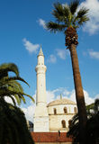 Kusadasi Mosque. Large traditionally styled turkish Mosque in Kusadasi, Aydin, Turkey, fronted by a Tall Palm tree against a clear blue sky Royalty Free Stock Photography