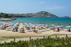 KUSADASI, TURKEY - AUGUST 20, 2017: Beautiful sand beach of Kusadasi with colorful straw umbrellas and lounge chairs, Aegean Sea. Turkey royalty free stock photography