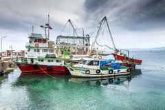 Kusadasi, Turkey, 05/19/2019: Fishing vessels in the port in the turquoise sea on a sunny day royalty free stock photography