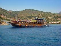Kusadasi Turkiet - Juni 17 2012: turist som har gyckel på ett litet kryssningfartyg som ankras nära stranden fotografering för bildbyråer