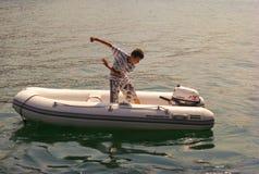 Kusadasi, Turquía - 17 de junio de 2012: un muchacho está encendiendo el motor externo del barco inflable Imagen de archivo libre de regalías